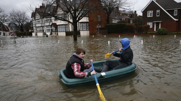 Two boys in a boat in a flooded street