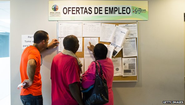 Puerto Ricans looking at an employment board