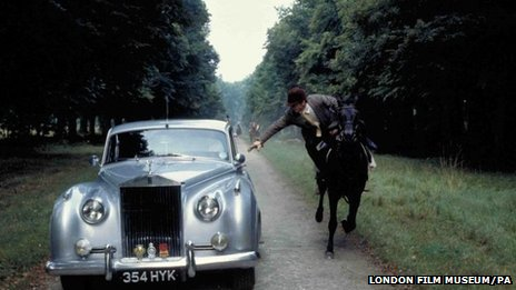 Roger Moore jumping from his horse to his Rolls Royce