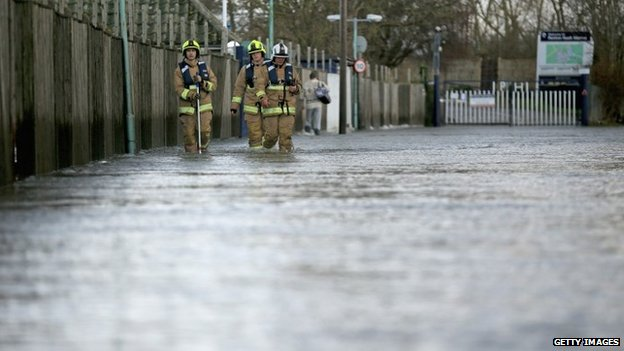 Firefighters walking down flooded street in Chertsey