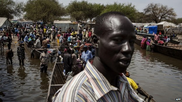 South Sudanese internally displaced people get on boats at Mingkaman's temporary camp, on 9 February 2014, as they head back to Bor
