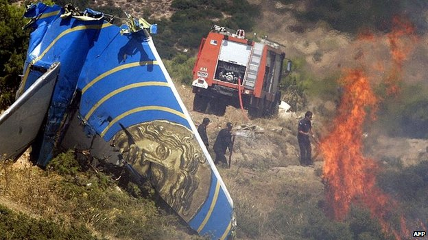 Firemen extinguish flames near the tail fin of the Helios passenger plane, Helios airways carrying 115 passengers and six crew which crashed into the mountains near Grammatiko some 45km north of Athens on  14 August 2005