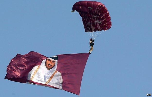 A paraglider pulls a flag showing Sheikh Tamim bin Hamad Al Thani on Qatar's National Day (December 2013)