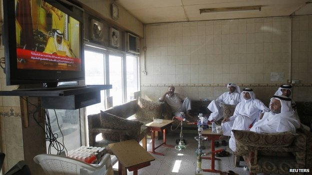 Qatari men watch a speech by Qatar's former emir in June 2013