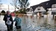 Residents wade through floodwater in the village of Wraysbury in Berkshire