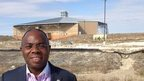 Pastor James Fadele stands in front of a church being built in Floyd, Texas