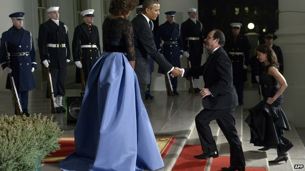 US President Barack Obama and First Lady Michelle Obama welcome French President Francois Hollande as he arrives for a state dinner at the White House in Washington, DC, 11 February 2014