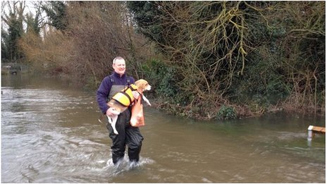 Darren Fuller, 48, takes his dog to the vet through flood water in Shepperton