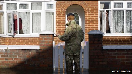 A British army soldier speaks to an Egham resident whose house is surrounded by flood water