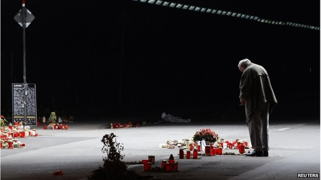 On 3 September 2010, a man stands in front of candles and flowers in the tunnel in which 21 people died during the 2010 Love Parade music festival.