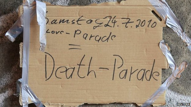 "Days after the tragedy, a placard attached to the tunnel wall reads ""Saturday 24 July 2010 Love-Parade = Death-Parade"""
