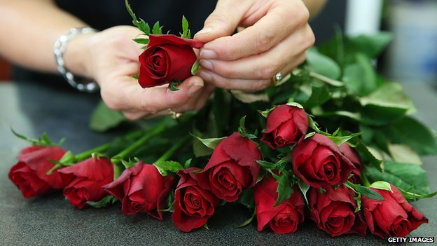A florist prepares a bunch of roses