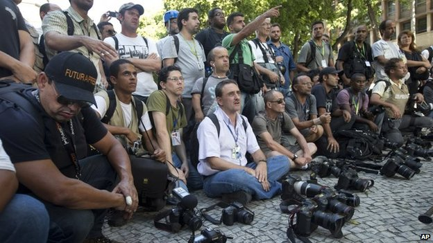 Journalists put their cameras down for one minute, to draw attention to the case of a cameraman who was killed by a flare while covering a protest last week in Rio de Janeiro