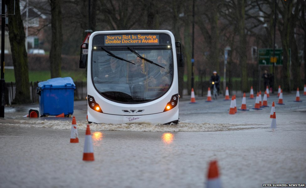 A bus makes its way through flood water in the town centre in Worcester, England