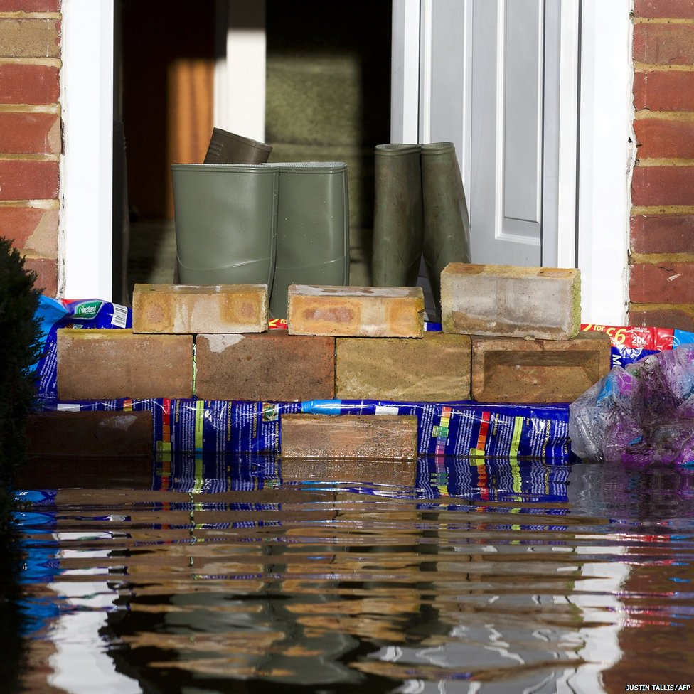 A wall of bricks is placed on a front door step in an effort to prevent floodwaters from entering the property in Egham