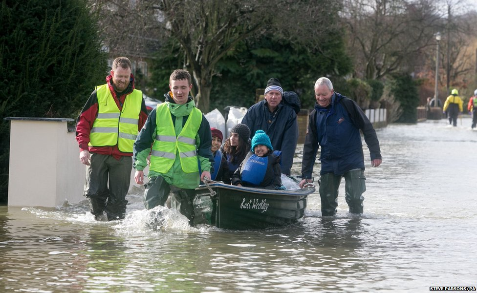 Residents pull a boat through flooding in Wraysbury, Berkshire