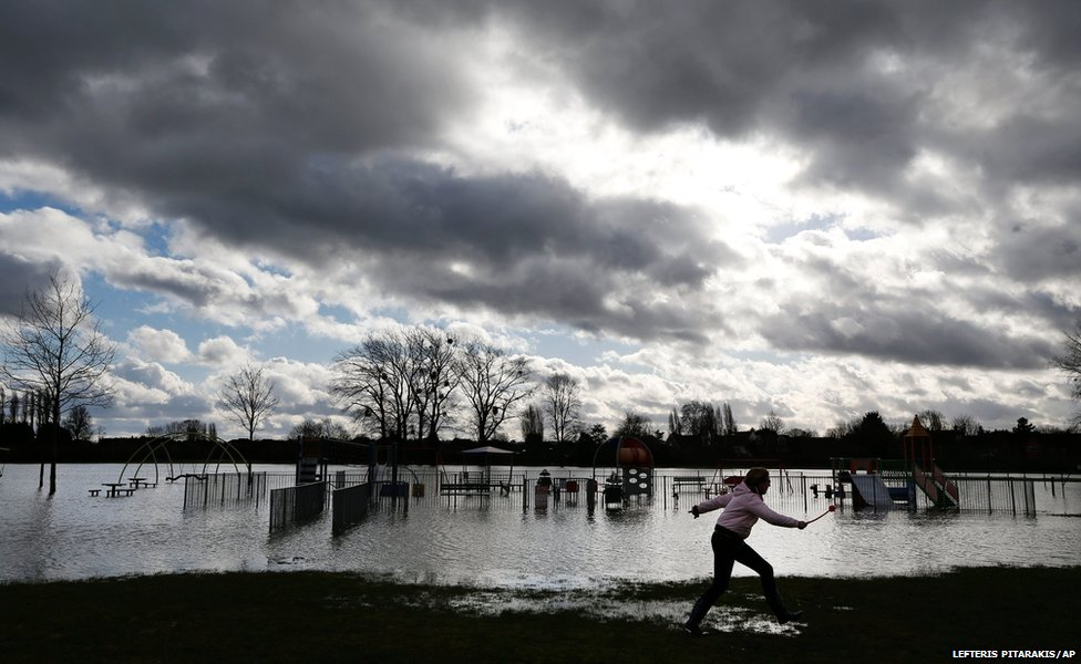 A woman runs as she plays with her dog on a flooded park in the village of Datchet, England