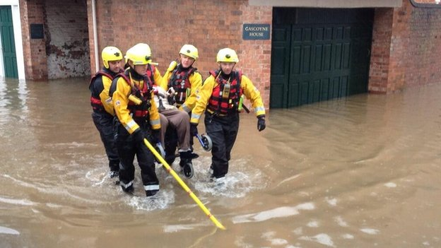 Lady in wheelchair carried through flood