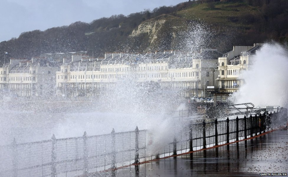 Waves crash over the promenade in Dover, Kent