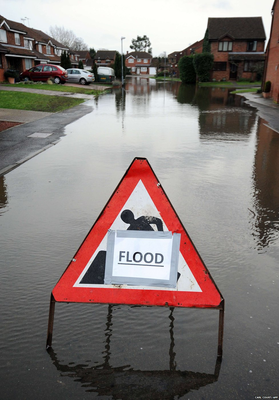 A sign warns of a flooded road on a housing estate near Windsor