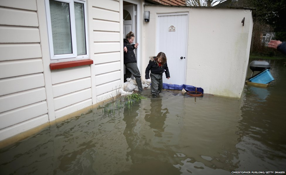 Children leave a flooded home in Staines