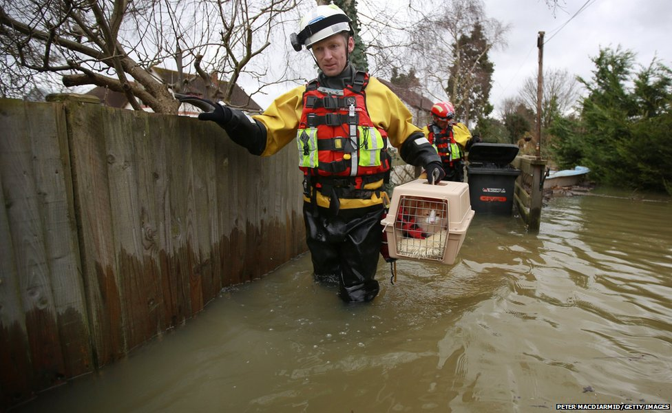 Inspector Alan Barnes of the RSPCA water rescue team evacuates a pet cat called Mac from a house in a flooded area next to the River Thames  in Wraysbury