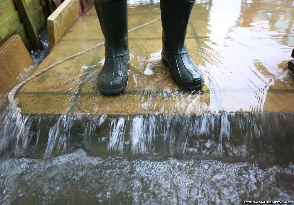 Flood water pours past the waders of resident Ian Richardson in his back garden in Wraysbury, England