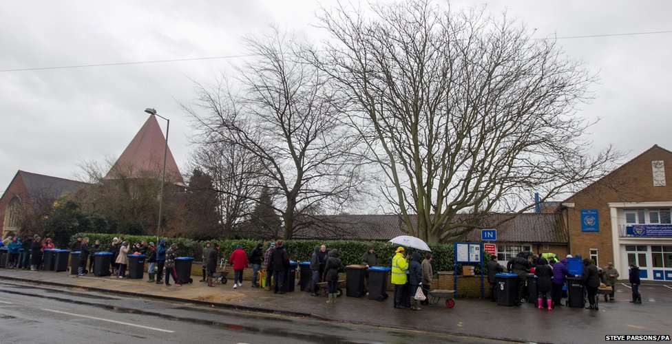 Residents queue for sandbags at the Magna Carta School in Egham,