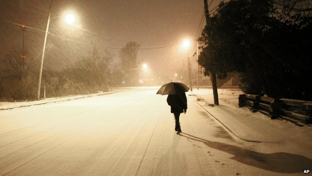 A woman walked down a snowy street in Greenville, Mississippi, on 11 February 2014