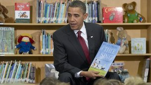 President Obama holding a copy of the book Of Thee I Sing: A Letter to My Daughters