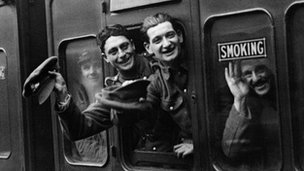 Soldiers wave from train window
