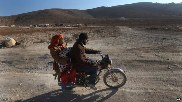 A Syrian man with his wife and child ride a motorcycle as they flee from Yabroud, the last rebel stronghold in Syria's mountainous Qalamoun region, on their way to the Lebanese-Syrian border town of Arssal, in eastern Lebanon, on Wednesday