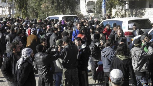 Civilians gathered near Syrian Arab Red Crescent and United Nations vehicles wait to be evacuated from a besieged area of Homs on Wednesday