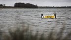"A yellow sign saying ""Danger"" is nearly submerged by water."