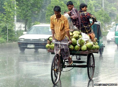An Indian man riding a rickshaw in a monsoon