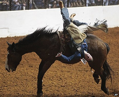 A man is upside down as he is thrown from a bucking horse at a rodeo