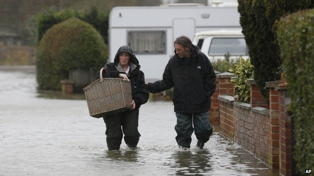 Residents in Egham make their way through a flooded street