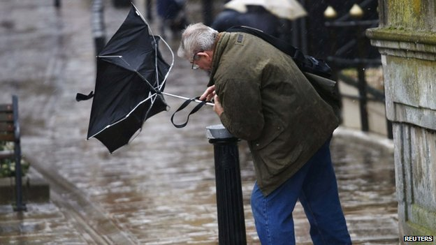 A man struggles to control his umbrella in Windsor, Berkshire
