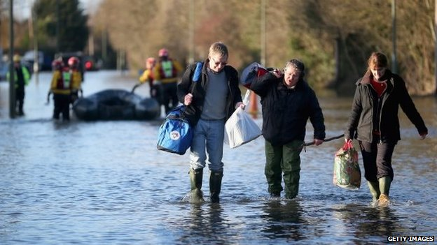 Residents in Chertsey wade through the floods carry their belongings after evacuating their homes