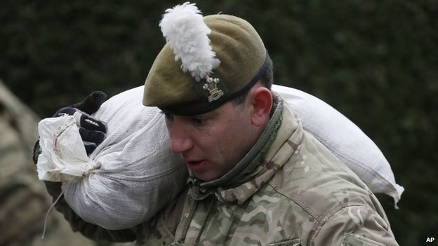 A British Army soldier carries a sandbag over his soldier