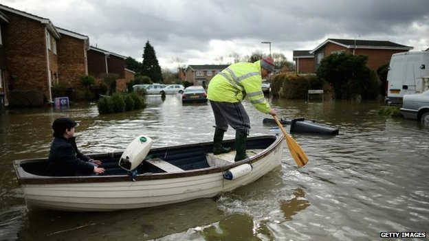 A man uses a paddle to steer a rowing boat through the flood water while a passenger looks on