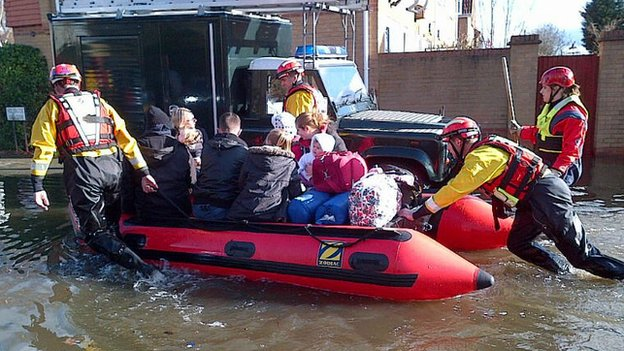 A specialist rescue team push a family through flood water on a boat