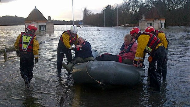 A couple are helped out of a boat by a recue team as they reach dry land
