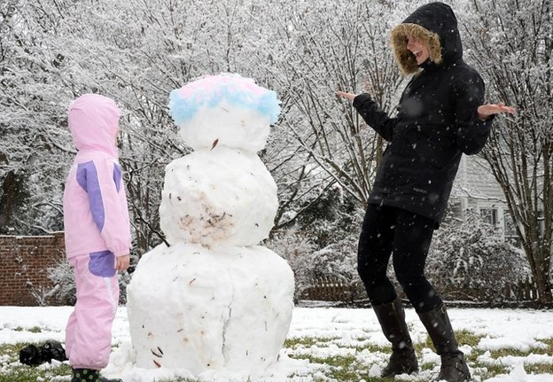 Jordan Larson-Horstman and her daughter Jane, 4, build a snowman in Charlotte, North Carolina, on 11 February 2104