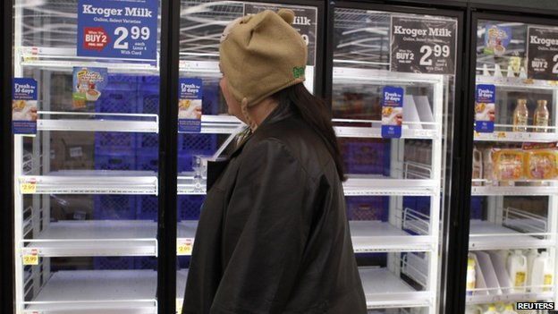 A shopper passes by mostly empty refrigerators of milk at a grocery store in Lilburn, Georgia, on 12 February 2014