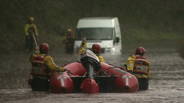 Firemen with dinghy wading out to van