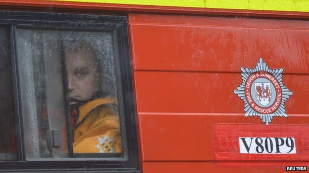 A member of Devon and Somerset Fire and Rescue Service looks out through the rain in his vehicle in the village of Thorney on the Somerset Levels