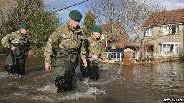 Royal Marines from 40 Commando wade past flooded properties in Moorland