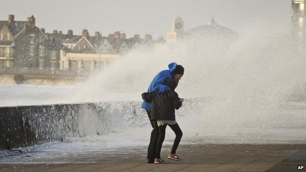 Two people struggle to make their way along the Esplanade, in Porthcawl, South Wales