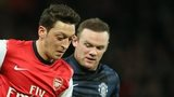 Arsenal playmaker Mesut Ozil battles with Manchester United forward Wayne Rooney